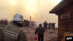A firefighter and local residents battle a fire in a village in the Khakasia region in southeastern Siberia, earlier this week.