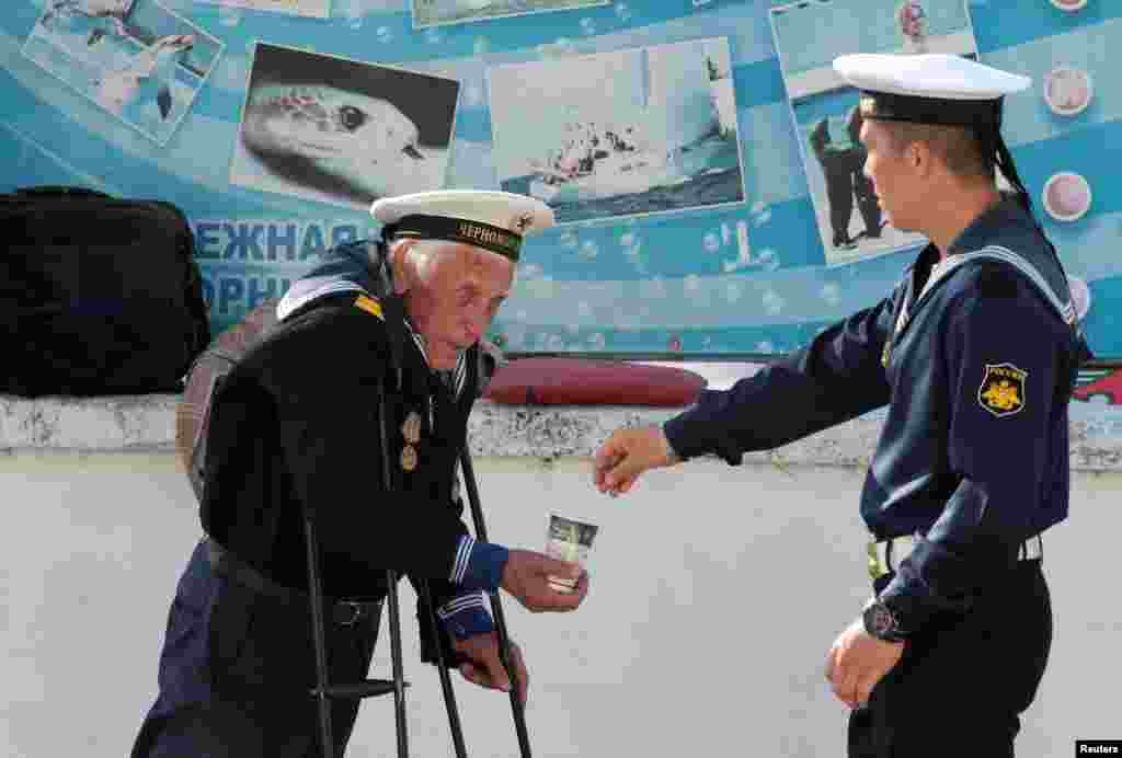 A Russian Navy serviceman gives alms to a beggar on an embankment of the Black Sea port of Sevastopol in the annexed Crimea Peninsula. (Reuters/Pavel Rebrov)