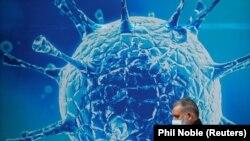 Человек, одетый в защитную маску, проходит мимо иллюстрации вируса за пределами регионального научного центра.