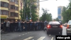 Russia - russian police officers are taking migrants to police station in the street