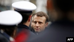 French President Emmanuel Macron speaks with policemen during a commemorative ceremony to mark the third anniversary of the attack on Charlie Hebdo magazine in Paris.