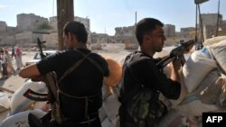 Syrian rebels man a checkpoint in Aleppo.