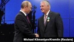 Владимир Путиннің (cол жақта) Ресей премьер-министрі кезінде Exxon Mobil басшысы Рекс Тиллерсонмен кездескен сәті. Ресей, Сочи, 30 тамыз 2011 жыл.