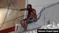 Aleksei Makeyev sits on a fence atop a building while covered in blood after an angry mob tried to lynch him for reportedly insulting Mexican people in Cancun on May 19.