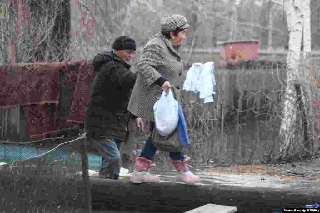 Некоторые жители всё еще с трудом, по искусственным насыпям и бревнам, добираются до своих дворов.