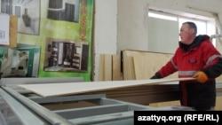 Столярный цех: работник распиливает листы фанеры для будущего шкафа.