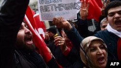 Protesters shout slogans and wave Turkish national flags in front of the Dutch Consulate in Istanbul on March 12.