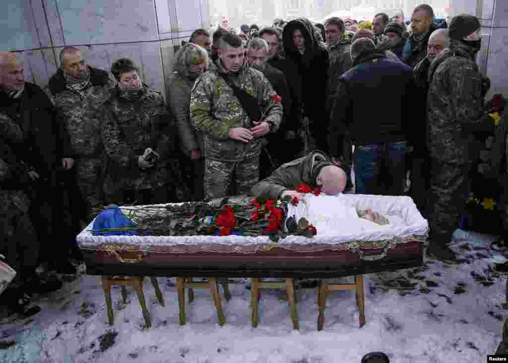 People take part in a funeral ceremony for Oleksandr Ilnytskiy, a member of a police special battalion Myrotvorets (Peacemaker), who was killed in the fighting in eastern Ukraine, on Independence Square in central Kyiv, on January 11. (Reuters/Gleb Garanich)