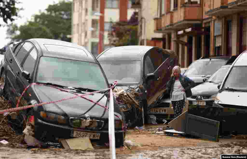 A woman speaks on the phone next to damaged cars after a heavy rainfall in Tafalla, Spain. (Reuters/Susana Vera)