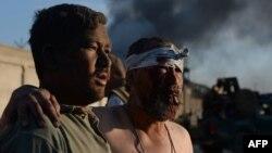 Мужчина ведет пожилого человека, раненного в резульате атаки смертника. Кабул, 2 июоя 2013 года. Иллюстративное фото.