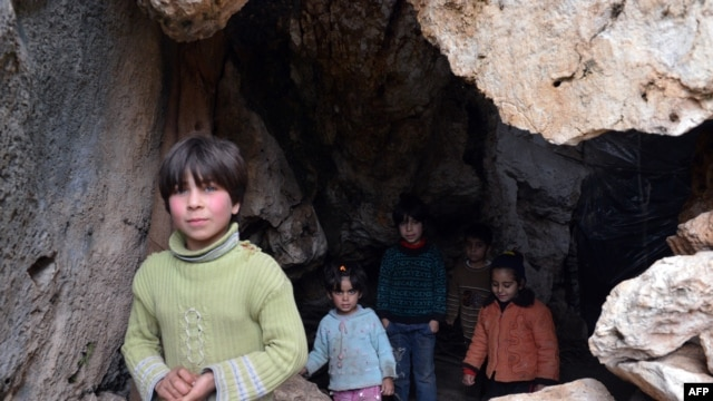 Syrian children, who evacuated their home due to shelling by regime forces, stand at the entrance of a cave in which they refuge in Ain al-Zarka northeast of Syria.