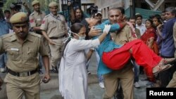 A nurse tries to assist as an Indian policeman carries a victim of the September 7 blast outside the High Court in New Delhi toward a hospital.