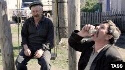 Мужчины пьют водку на скамейке у своего дома. Курган, 31 октября 2010 года.