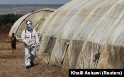 """Сотрудник Сирийской гражданской обороны (""""Белые каски"""") проводит санобработку палаток в лагере для беженцев в зоне Идлиба. 28 марта"""