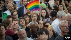 US -- People wave flags during a vigil in reaction to the mass shooting at a gay nightclub in Orlando, Florida,in New York on June 12, 2016. Fifty people died when a gunman allegedly inspired by the Islamic State group opened fire inside a gay nightclub
