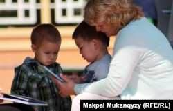 Женщина с детьми в мобильной библиотеке. Алматы, 12 июля 2012 года.