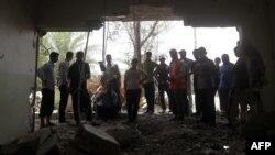 مواطنون يتفحصون آثار تفجير إستهدف منزلاً جنوب بغداد
