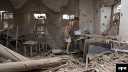 Женщина в разрушенном доме в поселке Сартана близ Мариуполя, 17 августа 2015 года.