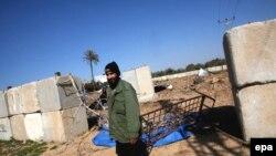 شبهنظامی حماس در برابر یکی از ساختمانهای این گروه که هدف موشک اسرائیل قرار گرفته است.