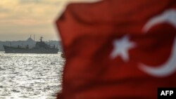 A Turkish flag flies on a ferry as Russian warship, the BSF Saratov 150, sails through the Bosphorus off Istanbul en route from the Black Sea to the eastern Mediterranean late last year.