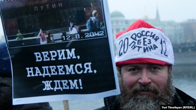 "One of the tens of thousands of Moscow protesters holds a sign saying: ""We believe, we hope, we wait!""  His hat says: ""Russian without Putin"" 2012."