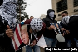 Palestinians holds posters of U.S. President Donald Trump during a protest in the West Bank City of Ramallah on December 6.