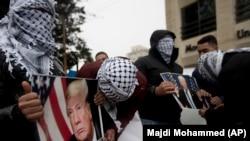 Palestinezët mbajnë në duar fotografi të presidentit Donald Trump, gjatë një proteste në qytetin Ramallah më 6 dhjetor.