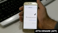 A man holds a smartphone connected to a Wifi network without internet access at an office in the Iranian capital Tehran on November 17, 2019.