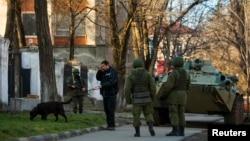 Вооруженные люди в военной одежде без опознавательных знаков на улице в Симферополе, рядом с украинской военной базой. 19 марта 2014 года.