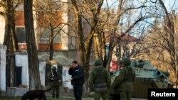 Кийиминде эн белгиси жок, бирок орусиялык деп эсептелген аскерлер Симфереполдогу Украин армиясынын базасын күзөтүүдө. 19-март, 2014.