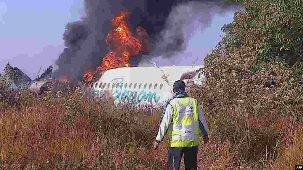 A man walks near the fuselage of an Air Bagan passenger plane after it crashed near Heho airport in Burma's eastern Shan state on December 25, killing two people and injuring 11.