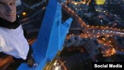 """Un presupus """"selfie"""" al lui Mustabg Wanted pe steaua vospită în culorile naționale ucrainene a unuia din zgîrie-norii staliniști de la Moscova."""