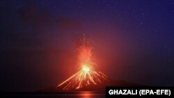 A photo taken with a slow shutter speed shows lava streams down the Mt. Anak Krakatau volcano during an eruption as seen from Rakata island in Lampung Province, Indonesia. (EPA-EFE/Ghazali)