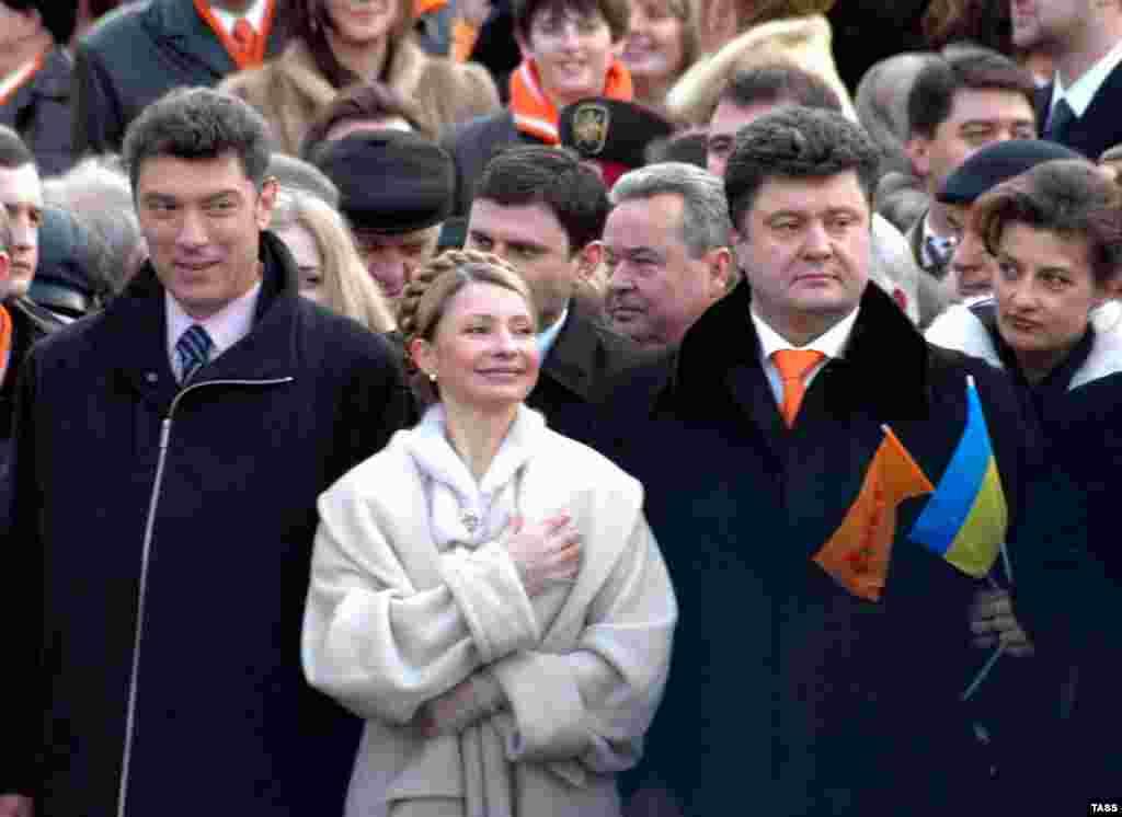 Немцов разговаря с Юлия Тимошенко на церемонията по встъпване в длъжност на украинския президент Виктор Юшченко през 2005 г. От другата ѝ страна е бизнесменът Петро Порошенко, който стана президент на Украйна през 2014 г.