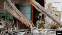 A boy stands at the doorway of his damaged house after it was hit by shelling in the separatist-controlled city of Donetsk on December 8.