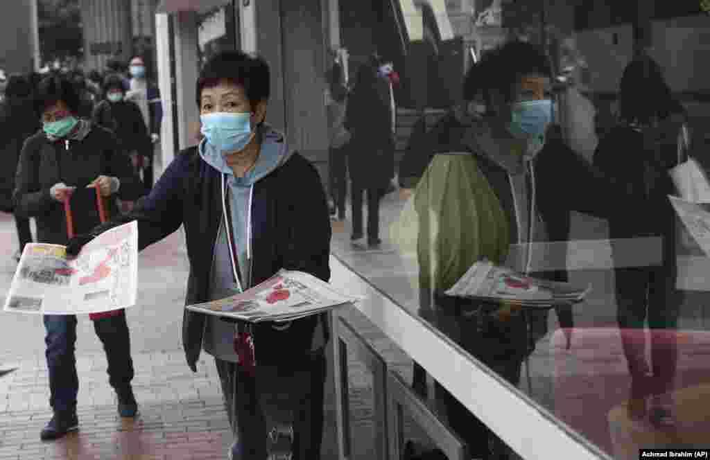 У Гонконгу жінки в захисних масках для обличчя роздають листівки про коронавірус в Ухані