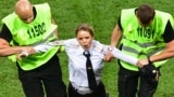 RUSSIA -- A pitch invader, a member of the Russian protest-art group Pussy Riot, is escorted by stewards during the Russia 2018 World Cup final football match between France and Croatia at the Luzhniki Stadium in Moscow on July 15, 2018.