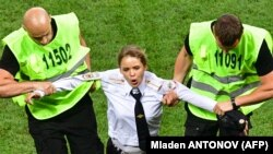 A member of Pussy Riot is apprehended by stewards after running onto the field at the final of the World Cup football match between France and Croatia in Moscow on July 15.