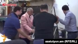 "Armenia - A screenshot of ""Zhoghovurd"" newspaper video of Vagharsh Abrahamian (second from left), the owner of a jewelry market in Yerevan, removing stalls used traders participating in anti-government demonstrations, 25Sep2014."