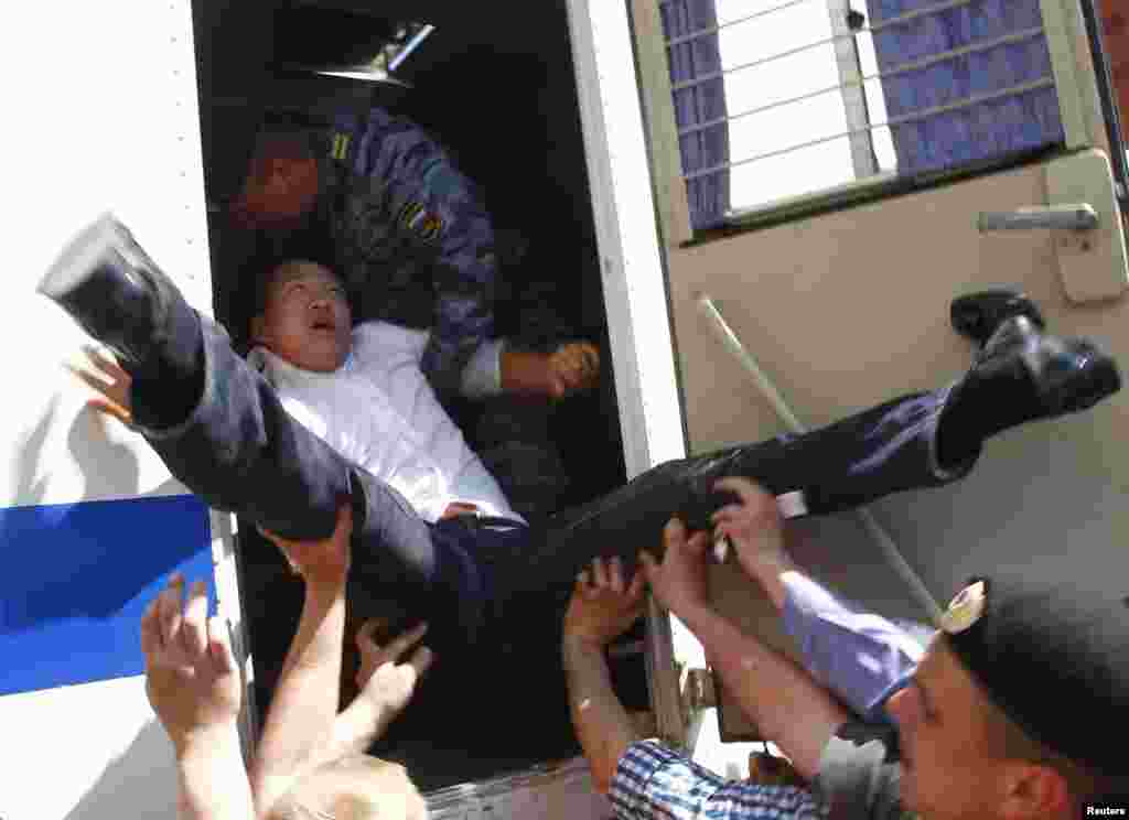 Police force gay-rights activist Daniel Choi into a police vehicle as they detain him near the Kremlin during an unsanctioned gay-pride parade in central Moscow on May 29, 2011.