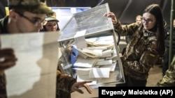 Ukrajinski vojnici sakupljaju listiće iz glasačke kutije tokom lokalnih izbora u Marinki na istoku Ukrajine, mart 2019.