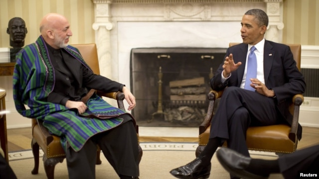 U.S. President Barack Obama (right) meets with his Afghan counterpart, Hamid Karzai, in the Oval Office of the White House in Washington on January 11.