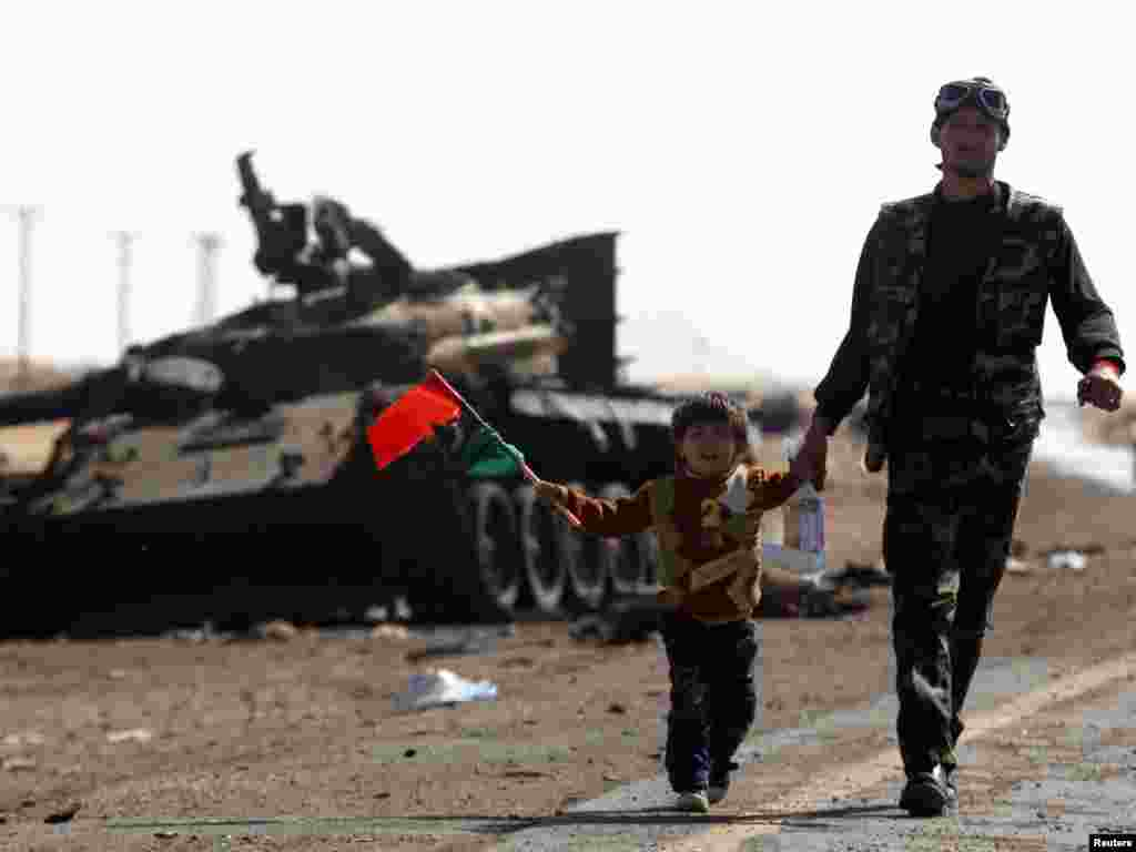 A rebel fighter escorts his son away from the front line at the western entrance of Ajdabiya on April 12. Forces loyal to Muammar Qaddafi bombarded the western entrance to the rebel-held town of Ajdabiya in eastern Libya. Photo by Yannis Behrakis for Reuters