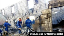 Ukrainian firefighters search through the rubble at an assisted-living facility for old people, where at least 17 died when a fire ripped through the building in the early hours of the morning on May 29.