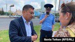 Представитель акимата города Нур-Султана Ерлан Отеулиев и прокурор Сарыаркинского района столицы Асет Дошаев (с телефоном в руке) беседуют с Анной Шукеевой.