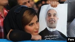 A supporter of Hassan Rohani holds a campaign poster of the candidate during a rally in Ahvaz in western Iran.