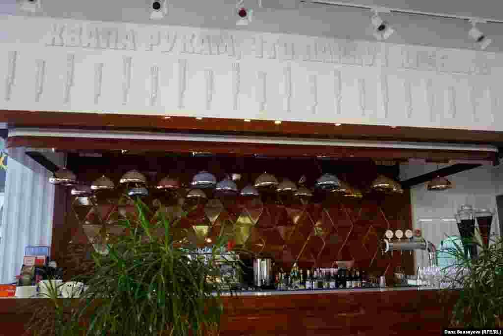 """Расположение и стойка бара в кафе """"Целинников"""" остались прежними со времен советской столовой. Над баром висит советский лозунг: """"Хвала рукам, что пахнут хлебом""""."""
