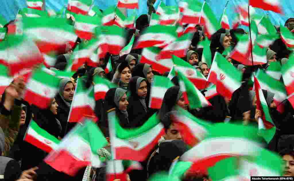 Female students wave national flags on Azadi (Freedom) Square.