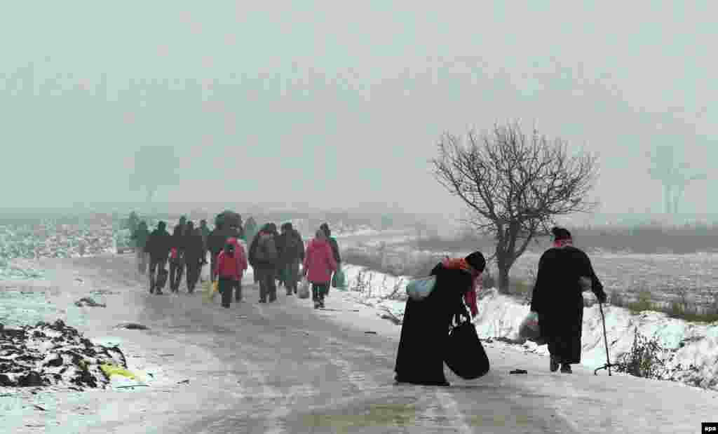 Migrants travel on foot from Macedonia to a camp for the temporary acceptance of migrants in the village of Miratovac on the border between Serbia and Macedonia, near to the southern Serbian city of Presevo. The number of migrants entering Serbia has not decreased, despite snow and low temperatures. About 1,000 migrants arrived from Macedonia by train on the morning of January 5. (epa/Djordje Savic)