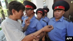 A demonstrator argues with police officers in front of the Belarusian Embassy in Bishkek, Kyrgyzstan in 2012.